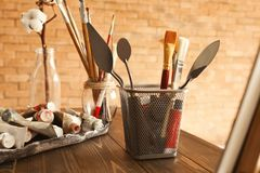Pinturas e ferramentas na tabela de madeira na oficina do artista imagem de stock