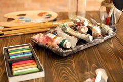 Pinturas e ferramentas na tabela de madeira na oficina do artista fotos de stock royalty free