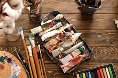 Pinturas e ferramentas na tabela de madeira na oficina do artista imagens de stock royalty free