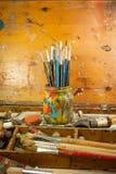 Pinturas e fontes da arte das escovas no estúdio da pintura Fotografia de Stock Royalty Free