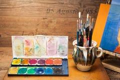 Pinturas e fontes da arte das escovas no estúdio da pintura Foto de Stock Royalty Free
