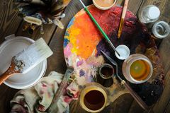 Pinturas, escovas, paleta em um fundo de madeira escuro imagem de stock royalty free