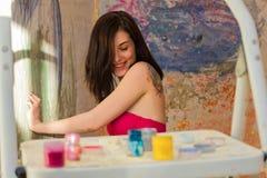 Pinturas hermosas del artista de la muchacha en la pared y las risas Fotos de archivo