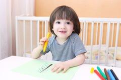 Pinturas lindas del niño pequeño con las plumas del fieltro Fotos de archivo libres de regalías