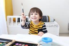 Pinturas sonrientes felices del muchacho con el cepillo Imágenes de archivo libres de regalías