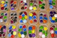 Pinturas vivo coloreadas del acrílico o de la témpera en las tazas, visión de arriba Foto de archivo