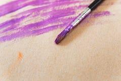 Pinturas y cepillo púrpuras con el lenguado Papel de Brown Espacio para el texto Imagen de archivo
