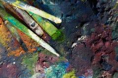 Pinturas y cepillos de aceite en el caballete y la paleta de colores viejos foto de archivo libre de regalías