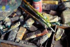 Pinturas y cepillos de aceite en el caballete y la paleta de colores viejos imagenes de archivo