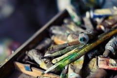 Pinturas y cepillos de aceite en el caballete y la paleta de colores viejos foto de archivo
