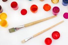Pinturas y cepillos en la opinión superior del fondo blanco Imágenes de archivo libres de regalías