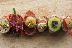 Pintxo设置了:橄榄,鲥鱼,西红柿,猕猴桃,葡萄干,治疗了火腿,蘑菇,在一个土气委员会的面包 免版税库存图片