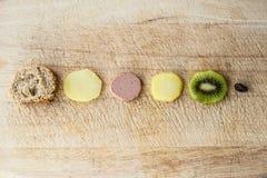 Pintxo-Schichten: Brot, Kartoffel, Paté, Kartoffel, Kiwi und Rosine auf einem rustikalen Brett Lizenzfreies Stockfoto