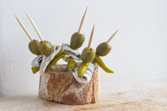 Pintxos Pintxo集合、橄榄、guindilla胡椒、鲥鱼和面包在一个土气委员会,食物从巴斯克地区 库存图片