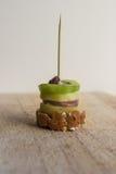 Pintxos Pintxo, uva passa, kiwi, patata, paté e pane su un bordo rustico, alimento dal Paese Basco fotografia stock