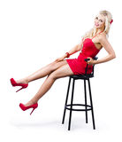 Pinup girl on a bar stool. Glamorous blond pinup girl in red dress and matching shoes posing on a bar stool  isolated on white background Stock Images