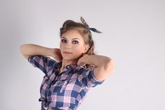Pinup beautiful woman with bow and in checkered shirt Stock Images