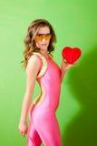Pinup dziewczyny mienia czerwony serce nad zielonym tłem Fotografia Royalty Free
