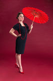 Pinup Girl in Black Dress Haughty with Red Parasol Stock Image