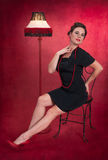 Pinup Girl in Black Dress with Lamp Stock Photo