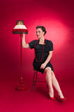 Pinup Girl in Black Dress Turns on Lamp Stock Photography