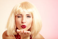 Pinup girl in blond wig retro dress blowing a kiss Royalty Free Stock Images
