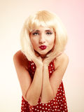 Pinup girl in blond wig retro dress blowing a kiss Royalty Free Stock Photography