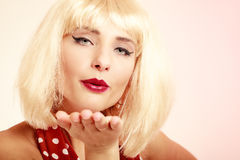 Pinup girl in blond wig retro dress blowing a kiss. Vintage pinup style. Portrait of stylish woman blowing a kiss on pink. Girl in blond wig and retro spotted stock photos