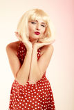 Pinup girl in blond wig retro dress blowing a kiss Stock Photos