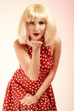Pinup girl in blond wig retro dress blowing a kiss Stock Photo