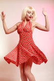 Pinup girl blond wig retro dress dancing. Party. Royalty Free Stock Image