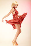 Pinup girl in blond wig retro dress dancing Stock Image
