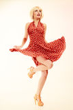 Pinup girl in blond wig retro dress dancing royalty free stock image