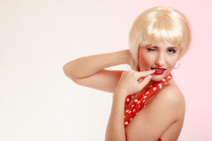 Pinup girl in blond wig and retro dress winking Royalty Free Stock Images