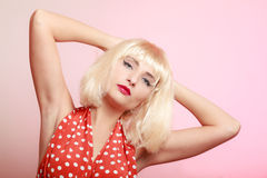 Pinup girl in blond wig retro red dress. Vintage. Stock Photo