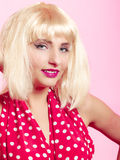 Pinup girl in blond wig retro red dress. Vintage. Royalty Free Stock Image