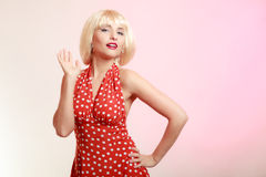 Pinup girl in blond wig retro red dress. Vintage. Stock Images