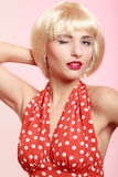 Pinup girl in blond wig and retro red dress winking. Vintage. Stock Photo