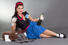 Pinup girl with bottle of champagne and packed suitcase Royalty Free Stock Photos