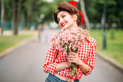 Pinup girl with bouquet of flowers, retro fashion royalty free stock photography