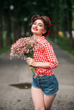 Pinup girl with bouquet of flowers, retro fashion stock photography