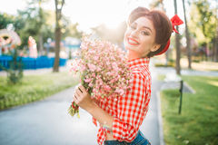 Pinup girl with bouquet of flowers, retro fashion. Pinup girl with bouquet of flowers, retro american fashion. Cute smiling woman in pin up style stock photography