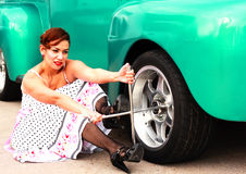 Pinup Girl Changing a Truck Tire Royalty Free Stock Photos