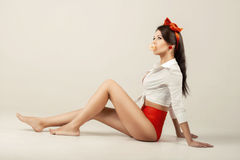 Pinup girl  with cud sitting in studio. Back to 1950s Royalty Free Stock Images