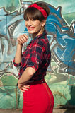 Pinup girl. Cute smiling brunette pinup woman wearing red headband, checked shirt and skirt with zip at the back. Over green and blue grafitti background royalty free stock images
