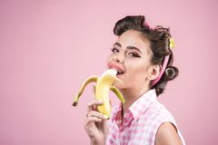 Pinup girl with fashion hair. pin up woman with trendy makeup. banana dieting. retro woman eating banana. pretty girl in. Vintage style, copy space. So tasty stock images