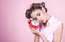 Pinup girl with fashion hair. pin up woman with trendy makeup. good morning. time management. retro woman with alarm. Clock. Time. sleepy tired girl in vintage royalty free stock image