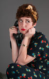 Pinup Girl in Flowered Outfit Bored While on the Telephone Royalty Free Stock Image