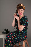 Pinup Girl in Flowered Outfit Grimaces While on the Telephone Stock Photo