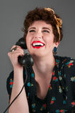Pinup Girl in Flowered Outfit Laughs on the Phone Royalty Free Stock Images